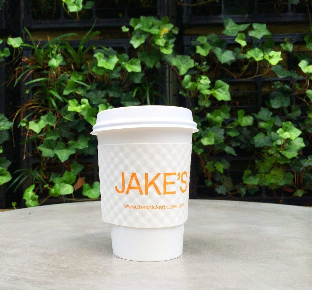 Closeup of Jake's coffee cup on table outdoors, plants in the background