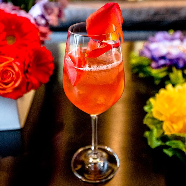 Closeup of cocktail with flower petal and flowers in the background