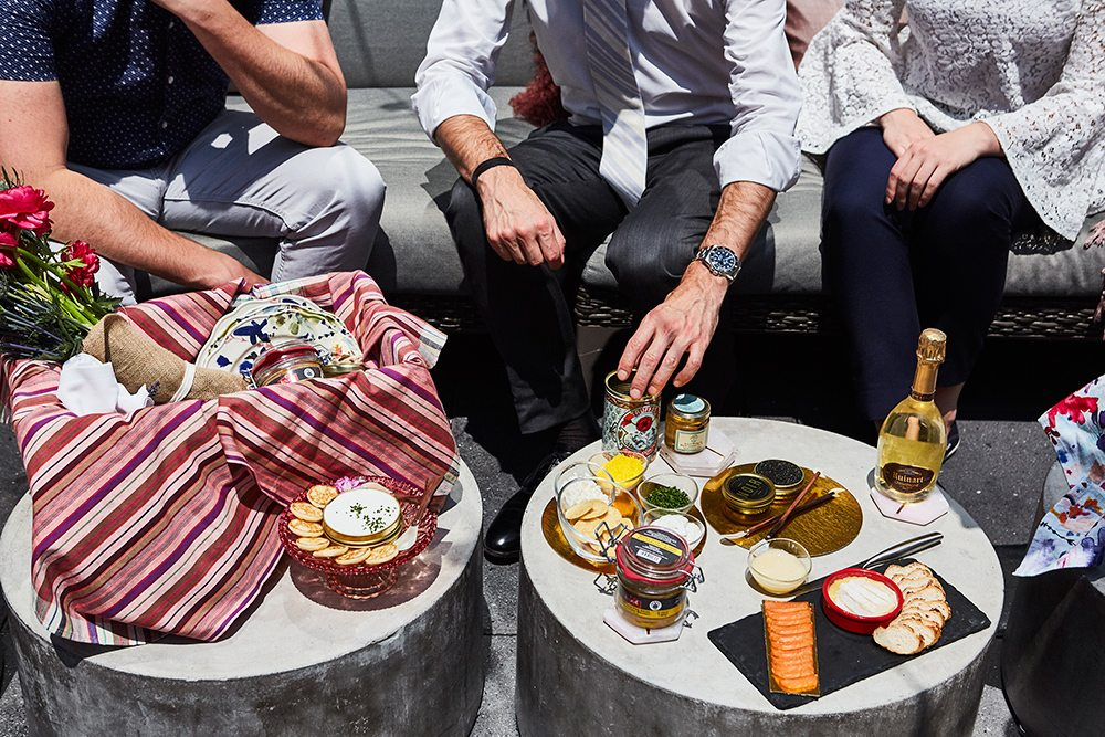 People seated around small tables, outdoors, sharing appetizers
