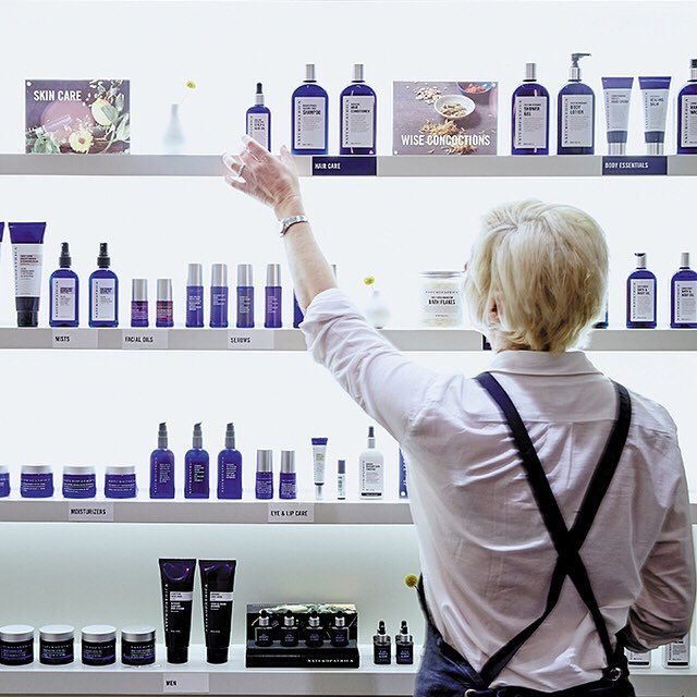 woman reaching for small bottle at shelf in spa