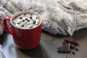 hot chocolate with marhmellow, chocolate chips and pieces of chocolate bars next to it