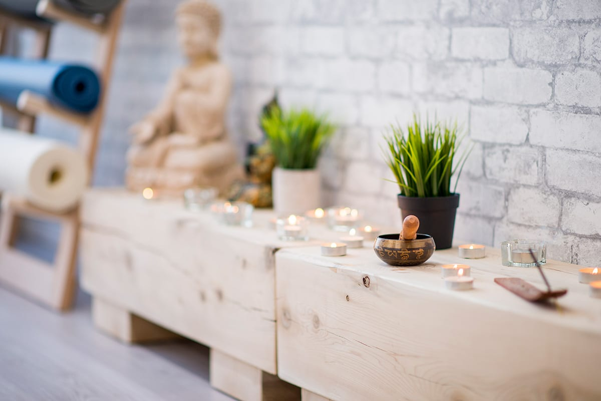 Yoga Studios with low tables with candles and Buddha statue