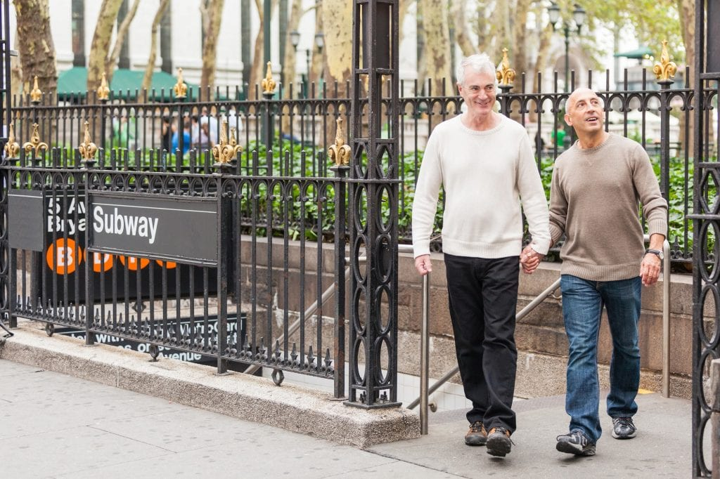Gay couple walking away from New York Subway entrance stairs