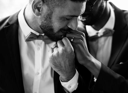 Man wearing tuxedo kissing hand of partner