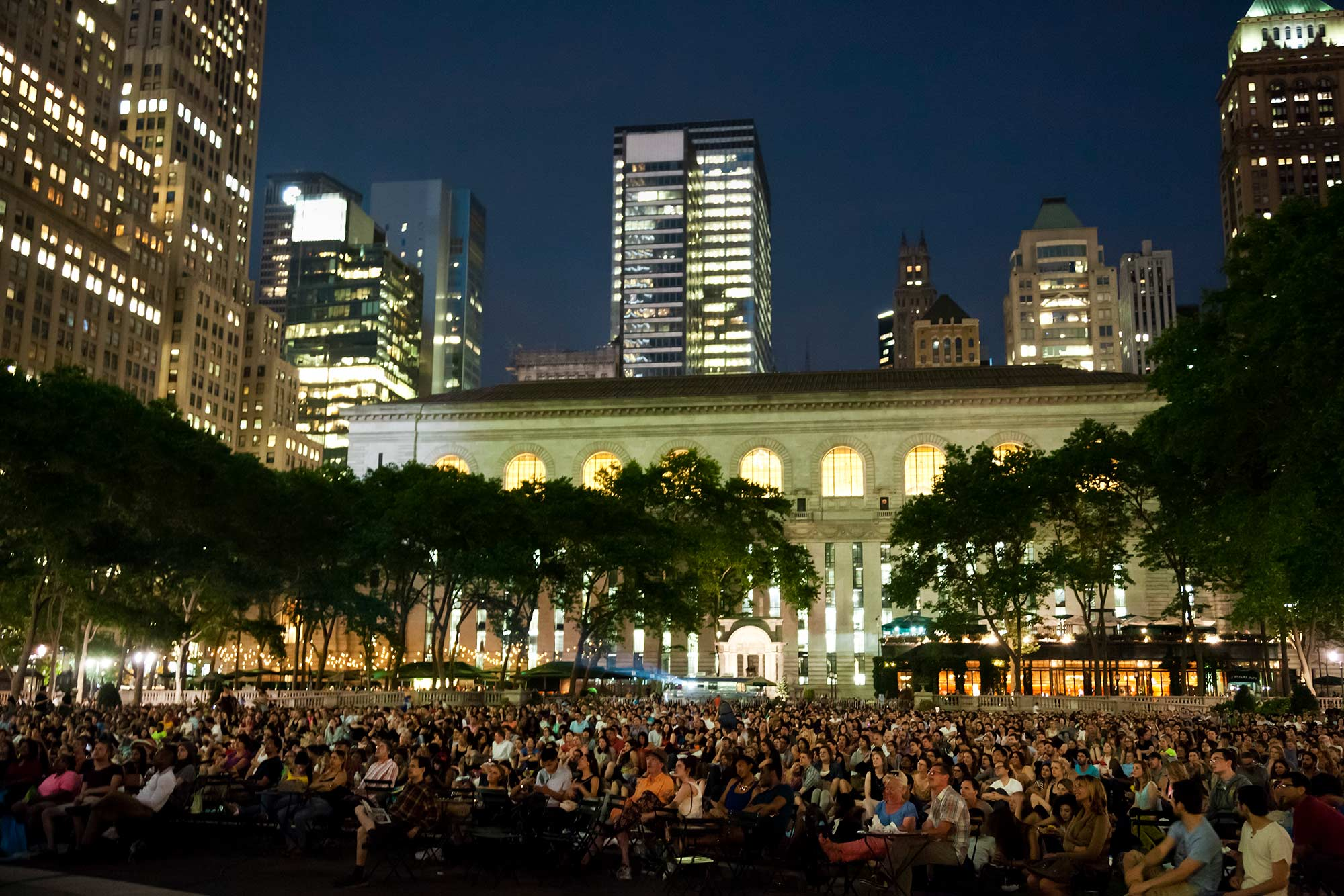 crowd sitting outdoors at nighttime at Bryant Park
