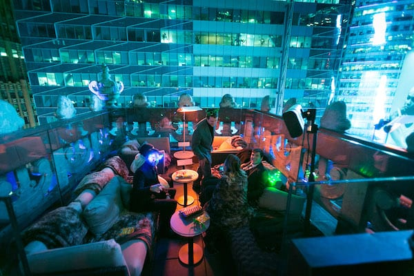 People sitting at sofas on a rooftop at night