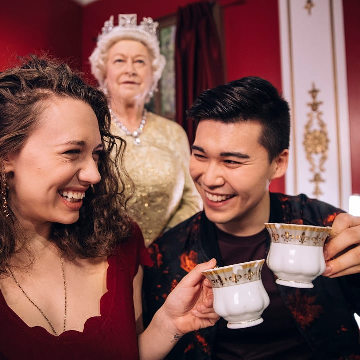 Couple smiling, holding teacups in front of wax statue of Queen Elizabeth at Madame Tussauds Museum in New York