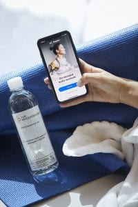 Hand holding a phone with the Aaptiv app, next to water bottle