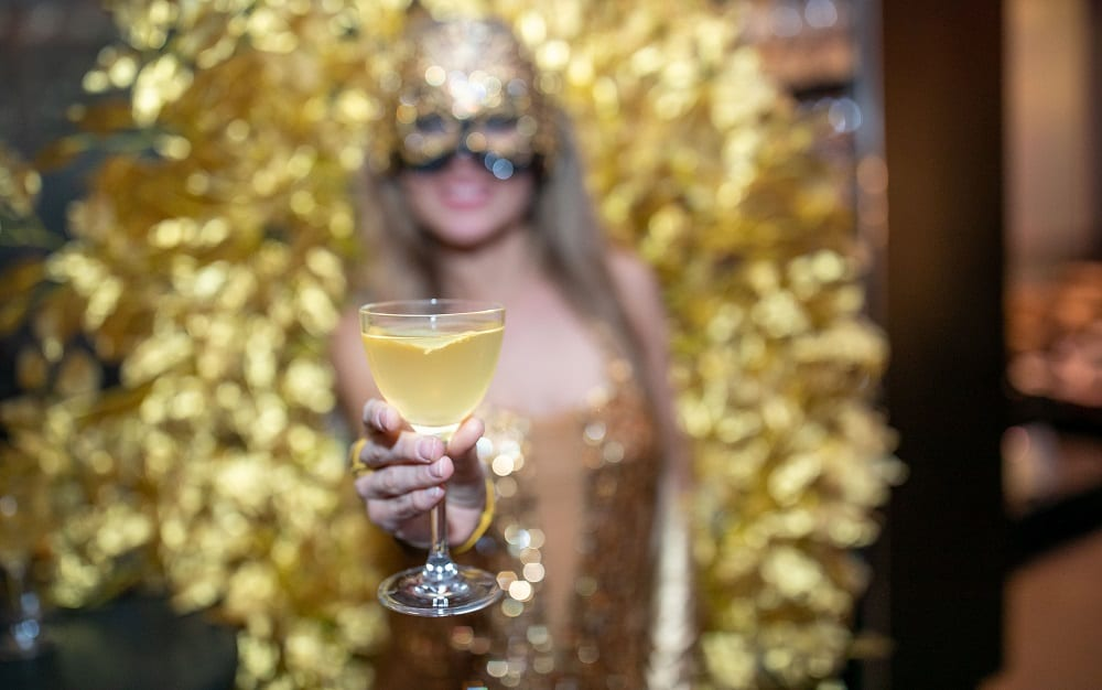 Woman wearing a mask holding up a cocktail glass