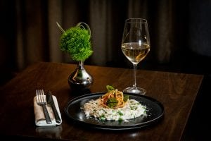 Dish on table with glass of wine and small plant decoration